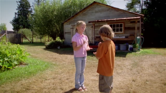 Girl and boy playing Rock, Paper, Scissors in front of garden shed