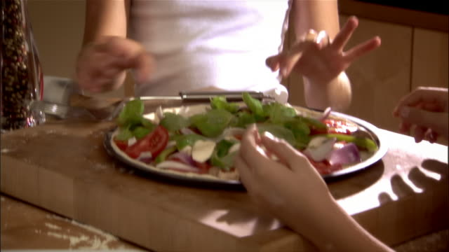 Girl and boy putting vegetable toppings on pizza