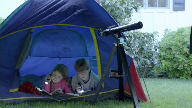 stockvideo's en b-roll-footage met ms girl (8-9) and boy (10-11) reading books using flashlights in tent in garden, encino, california, usa - tent