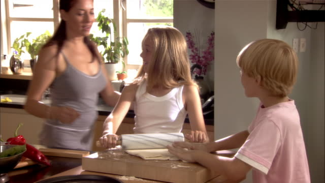 Girl and boy rolling dough in kitchen / mother coming over and showing them how to use rolling pin