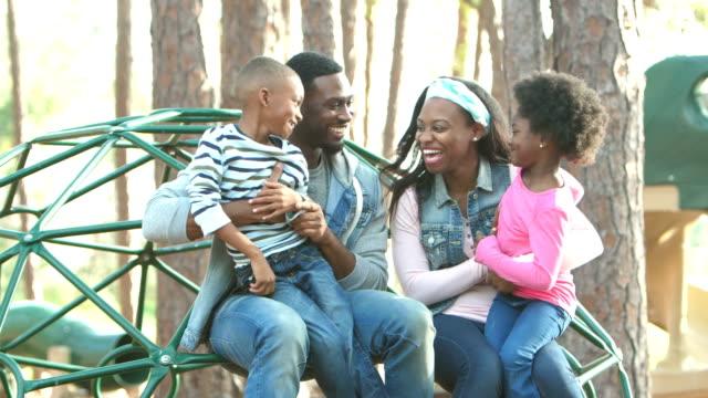 Meisje en jongen oplopen tot ouders op speelplaats