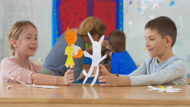 girl and boy sitting in the classroom and playing with paper puppets they made themselves - pupazzo video stock e b–roll