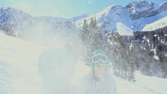 ms girl and boy (10-13) throwing snow at camera / alta, utah, usa - ユタ州 アルタ点の映像素材/bロール