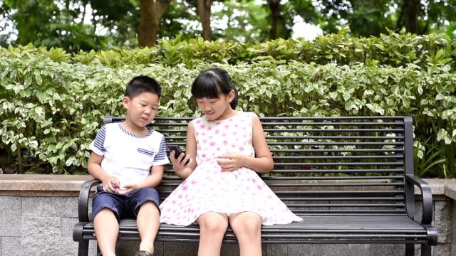 vídeos de stock e filmes b-roll de girl and boy using smart phone - banco de parque