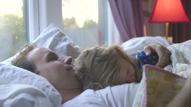 vídeos de stock e filmes b-roll de cu zo td girl and dad cuddling in bed / los angeles, california, united states - contente