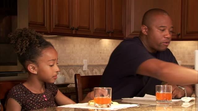 vídeos de stock, filmes e b-roll de cu girl (6-7) and father eating potato chips in kitchen / salt lake city, utah, usa - snack salgado