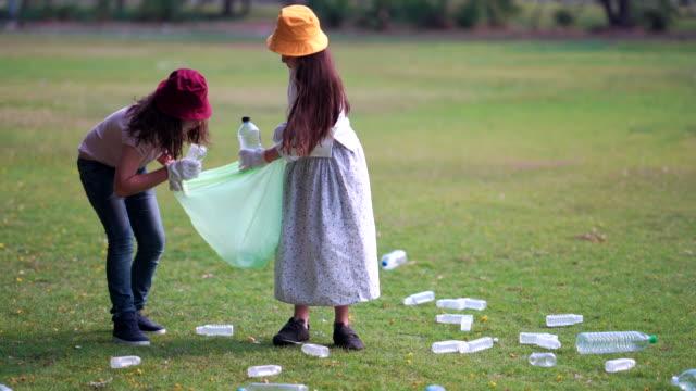 vidéos et rushes de la fille et l'ami aide à nettoyer le parc, ramassant ou récupérant des ordures outre du sol - collection