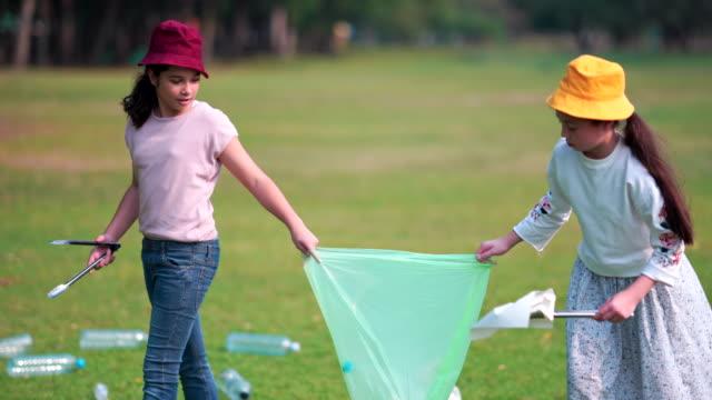 vídeos de stock, filmes e b-roll de menina e amigo ajuda a limpar parque, recolhendo ou lixo da coleta de lixo do chão - coleção