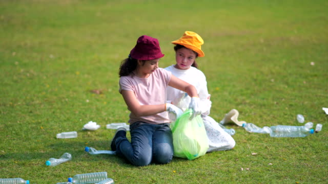 vídeos de stock e filmes b-roll de girl and friend helps to clean up park ,picking up or garbage collection rubbish off the ground - apanhar atividade física