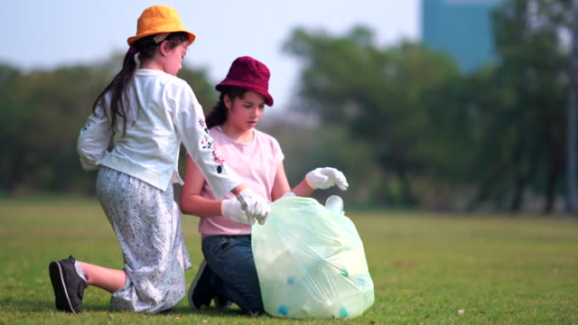 girl and friend helps to clean up park ,picking up or garbage collection rubbish off the ground - choosing stock videos & royalty-free footage