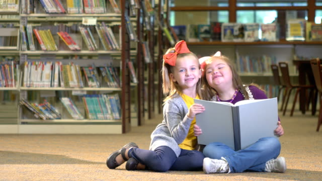 girl and friend with down syndrome reading book - learning disability stock videos & royalty-free footage