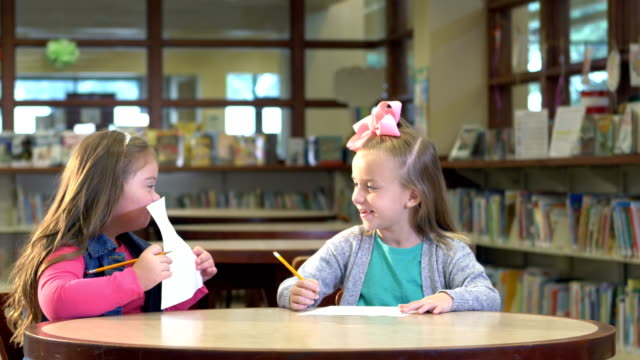 girl and friend with down syndrome writing in library - learning disability stock videos & royalty-free footage