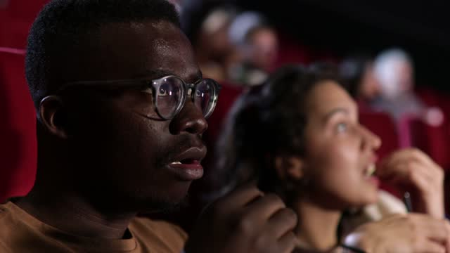 girl and her african american friend watching a serious movie at the cinema - film industry stock videos & royalty-free footage