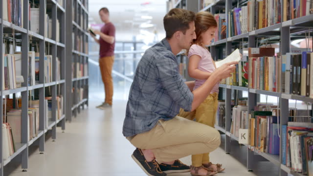 ds girl and her dad reading a book in a library aisle - library stock videos & royalty-free footage