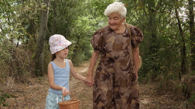 a girl and her grandmother walk the dusty country road. real people, rural scene, unusual angle. - cucina mediterranea video stock e b–roll