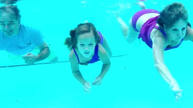 vídeos de stock, filmes e b-roll de menina e os seus avós natação subaquática - prendendo a respiração