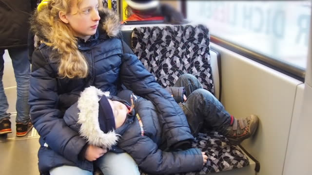 girl (13-14 years) and little child (4 years) lying on her sister while going in a tram at christmas time in germany, europe. - tram stock-videos und b-roll-filmmaterial