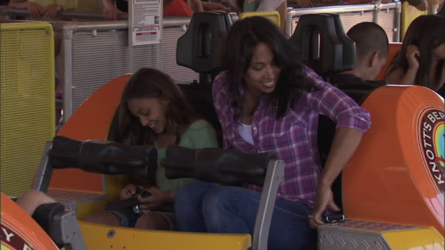 girl and mom takes seats on sidewinder roller coaster at knott's berry farm theme park - roller coaster stock videos & royalty-free footage