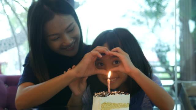 meisje en moeder genieten met de verjaardagstaart, met de hand spelen hart teken