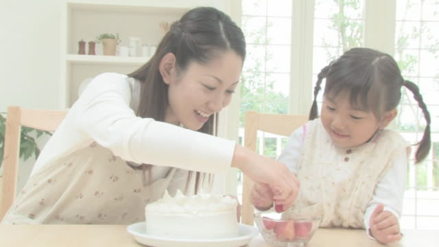 Girl and mother making cake