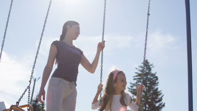 girl and mother on playground chain swing with sun flares - kinderspielplatz stock-videos und b-roll-filmmaterial