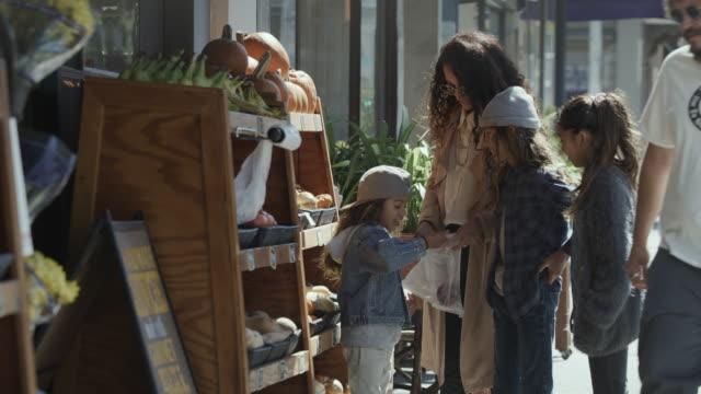 vídeos de stock e filmes b-roll de girl and mother placing vegetables in plastic bag at food display on city sidewalk / san francisco, california, united states - saco de plástico