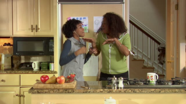 MS Girl and mother sharing headphones while dancing and singing in kitchen, then they hug / White Plains, New York, USA
