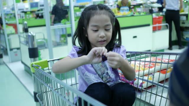 flicka och mor shopping, spendera pengar på kassan counter - kassa bildbanksvideor och videomaterial från bakom kulisserna