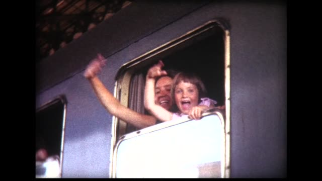 1963 girl and nanny wave goodbye from departing train window - auseinander stock-videos und b-roll-filmmaterial