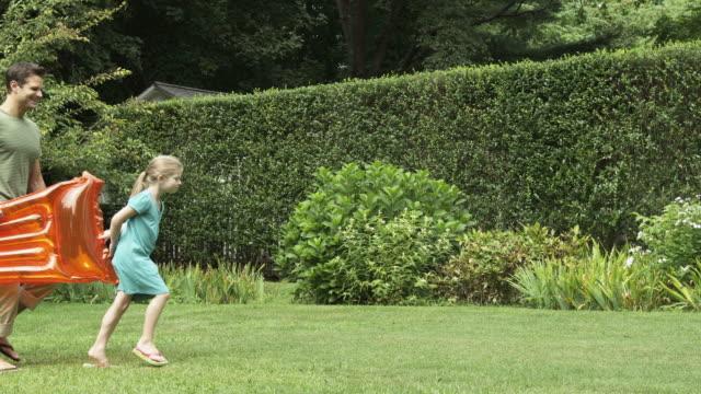 girl and parents carry inflatable mattress across garden - gå tillsammans bildbanksvideor och videomaterial från bakom kulisserna