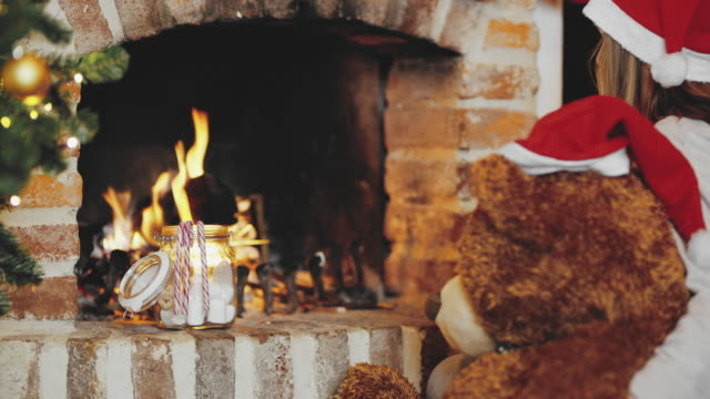 4K Girl and teddy bear in Santa hats eating marshmallows by fireplace, real time