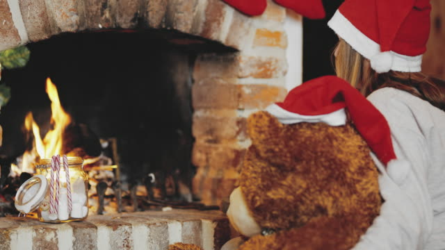 4K Girl and teddy bear in Santa hats relaxing by Christmas fireplace, real time