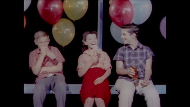 vidéos et rushes de 1958 a girl and two boys laugh as they eat snacks - perception sensorielle
