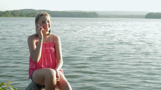ms pan girl (12-13) answering phone by lake / glen gardner, new jersey, usa - 12 13 år bildbanksvideor och videomaterial från bakom kulisserna