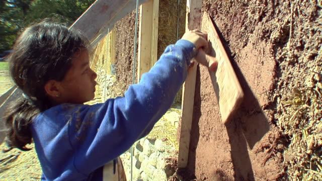 cu girl (6-7) applying adobe mud mixture to wall of straw house under construction, grass lake, michigan, usa - adobe bildbanksvideor och videomaterial från bakom kulisserna