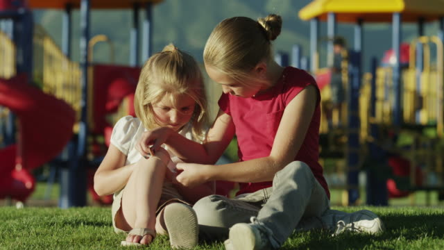 vídeos de stock, filmes e b-roll de ms girl (10-11) applying bandaid to another girl's (4-5) knee, sitting on grass at playground / orem, utah, usa - dano físico