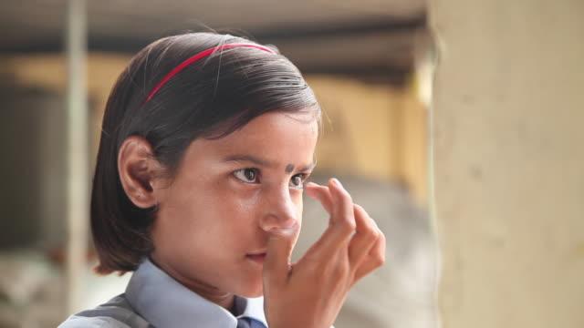 girl applying bindi on her forehead, faridabad, haryana, india  - bindi stock videos and b-roll footage