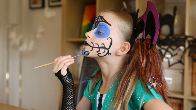 girl applying halloween face paints - audio available stock videos & royalty-free footage