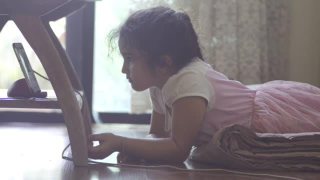 vídeos de stock, filmes e b-roll de garota está deitada no chão e usando tablet - temas fotográficos