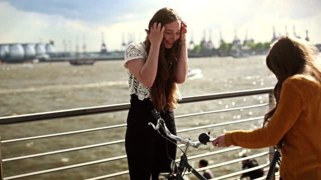 Girl arrives with bicycle to her friend