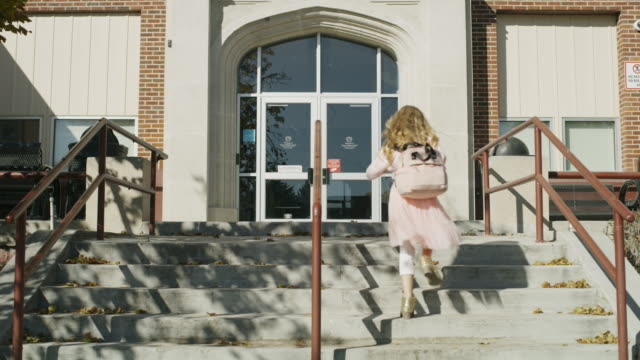 Girl arriving late at school running up staircase / Provo, Utah, United States