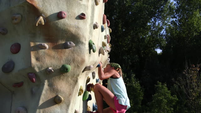 Girl ascending a climbing wall