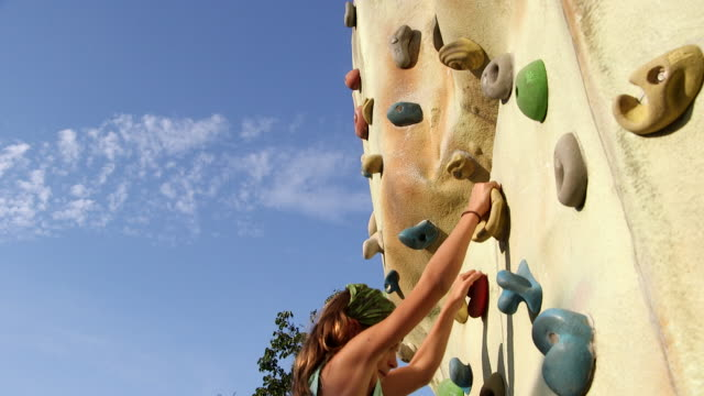 girl ascending a climbing wall - climbing wall stock videos & royalty-free footage