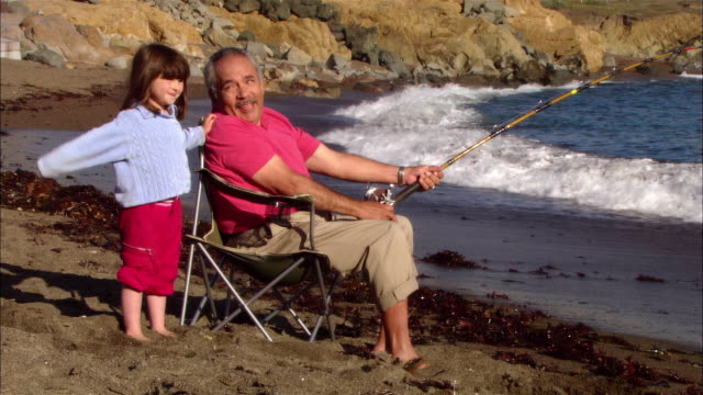 ms, girl (4-5) assisting grandfather wave fishing in rocky beach, moonstone beach, cambria, california, usa - 祖父点の映像素材/bロール