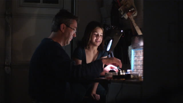 MS, PAN, Girl (10-11) assisting man working at workbench, Hollywood, California, USA