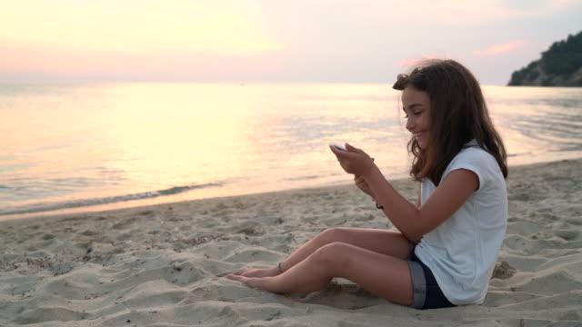 vídeos de stock e filmes b-roll de girl at beach holiday using modern technologies - 14 15 anos