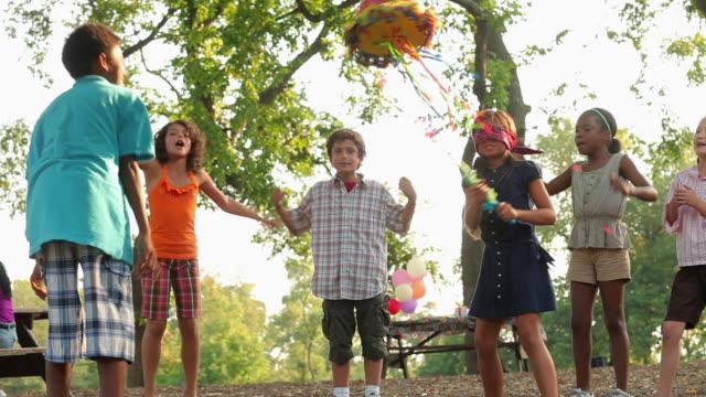 vídeos de stock e filmes b-roll de girl at birthday party hitting pinata - braço humano