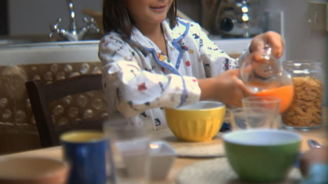 ms tu girl at breakfast table pouring orange juice, drinking it, and smiling/ rome, italy - beccuccio video stock e b–roll