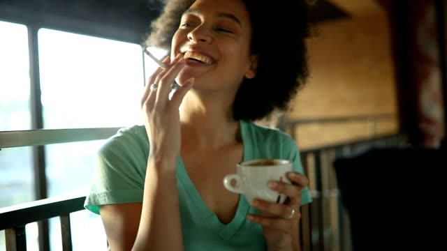 girl at the cafe drinking coffee and smoking with a friend - beautiful woman stock videos & royalty-free footage