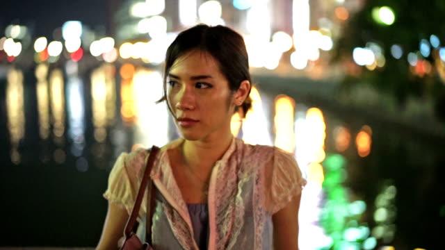 Rapariga na Riverside com espelho de tempo de noite cidade luz
